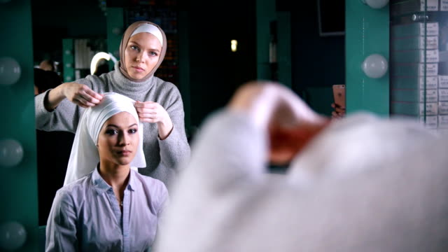Two muslim women in front of mirror to tie Islamic turban, preparing for a wedding video