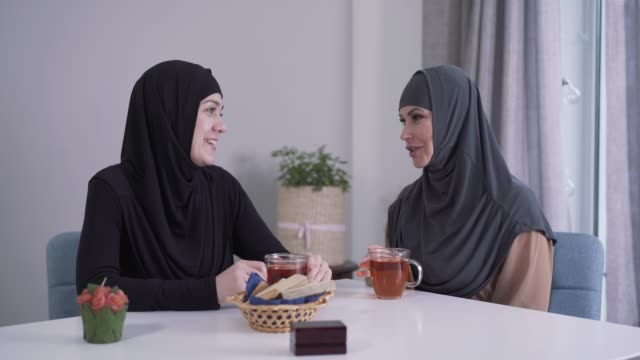 two muslim women in hijabs sitting at the table with tea and talking. positive young ladies gossiping indoors. eastern culture, communication, friendship. - abbigliamento religioso video stock e b–roll