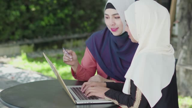 two muslim women shopping online with credit card and laptop. - online banking video stock e b–roll