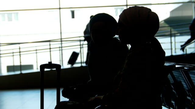 vídeos de stock e filmes b-roll de two muslim women talk to each other in the waitroom at airport - amizade feminina