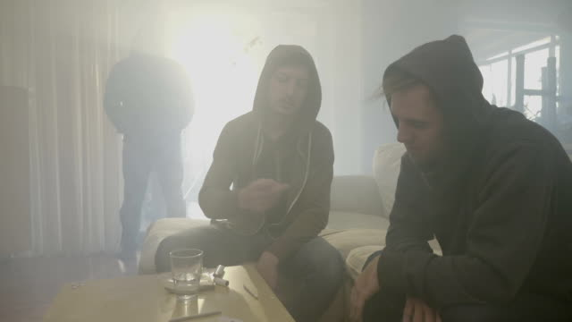 vídeos de stock, filmes e b-roll de dois rapazes de estupefacientes no capô partilha um baseado de maconha em um quarto fumegante, enquanto outro homem vem da janela e pedindo a erva - sem cultivo