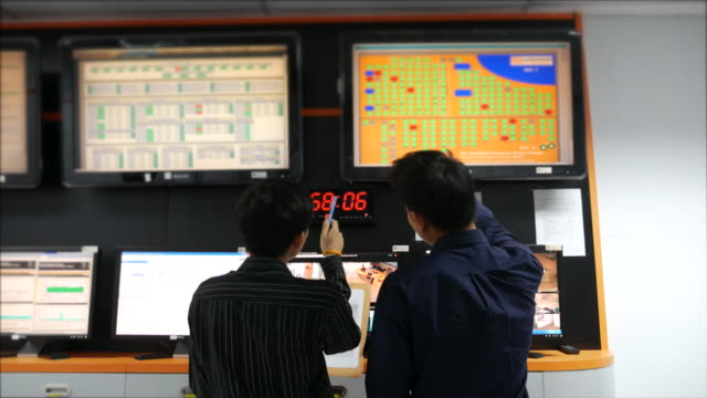 Two network engineer  working on System control room monitoring video