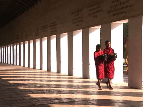 two novice monks walking down the hallway pal177 - burma home do stok videoları ve detay görüntü çekimi