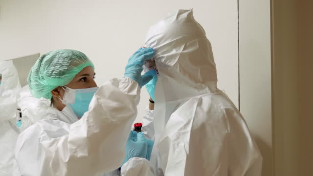 Two nurses helping each other with protective equipment at hospital corridor