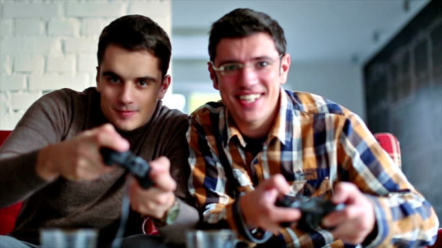 Two of friends playing video games Two of friends playing video games in the office relax room rivalry stock videos & royalty-free footage