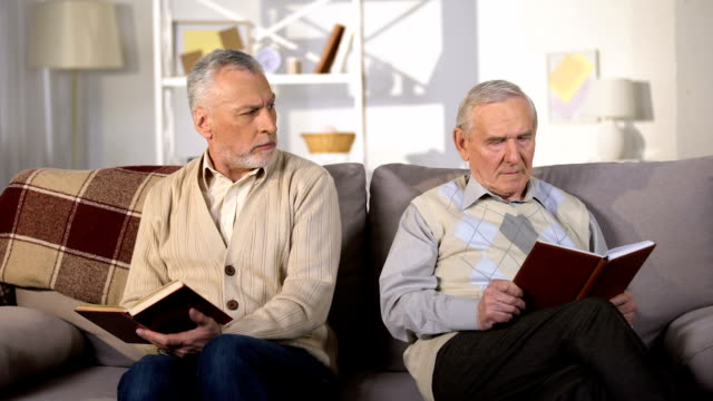 two offended male friends reading books on sofa at home, misunderstanding - chiedere scusa video stock e b–roll