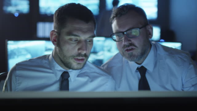Two office employees are having a conversation next to a computer in a dark monitoring room filled with display screens.