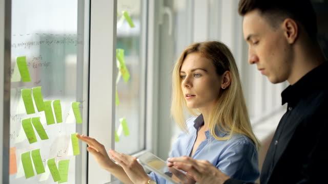 vídeos y material grabado en eventos de stock de dos trabajadores de oficina pegue calcomanías coloridas en ventana - eventos de etiqueta