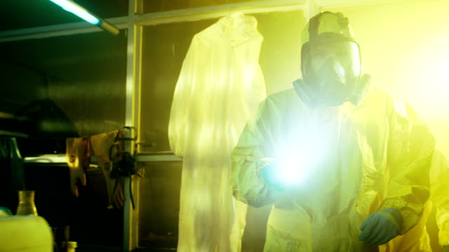 Two Officers from Hazardous Materials Police Unit Inspect Busted Drug Making Laboratory. They Wear Hazmat Suits and Gas Masks and Walk Carefully with Flashlights. video