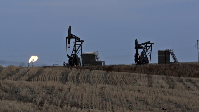 Two Oil Drilling Pump Jacks near Refinery Flames video