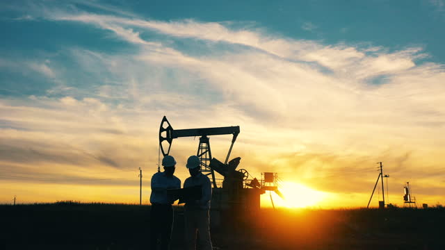 Two oil industry workers inspecting an oil field with a laptop at sunset video