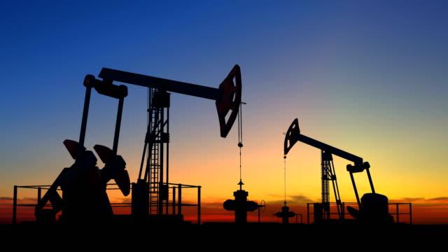 stockvideo's en b-roll-footage met twee de hefbomen van de oliepomp die ruwe olie onder mooie zonsonderganghemel winnen - olieraffinaderij
