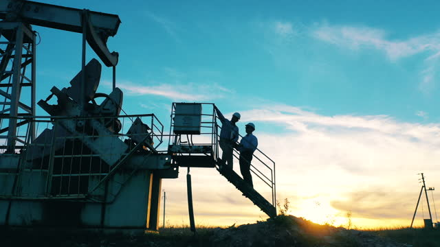 Two oil workers inspecting an oil field at bright sunset video