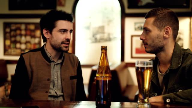 Dos viejos amigos están teniendo conversaciones en pub cerveza. Cristal y botella en primer plano, tablas y cuadros en las paredes de fondo. - vídeo