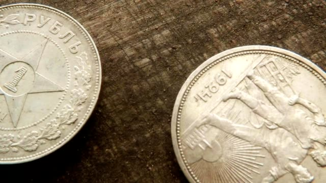 Two Old Soviet Silver Ruble Farmworkers on Obvers Fingers Turn One Coin Star on Wood Macro video