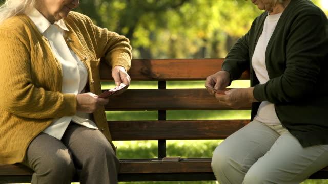 Dos ancianas disfrutar jugando en Banco de parque, amigos mayores ocio las cartas - vídeo
