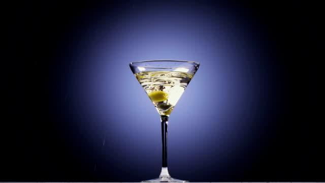 stockvideo's en b-roll-footage met twee olijven vallen in hoog glas met een cocktail. slow motion - martiniglas
