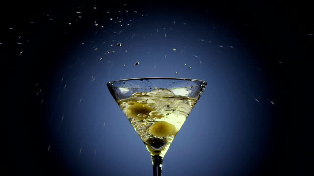 two olives fall into tall martini glass. black background - martini video stock e b–roll