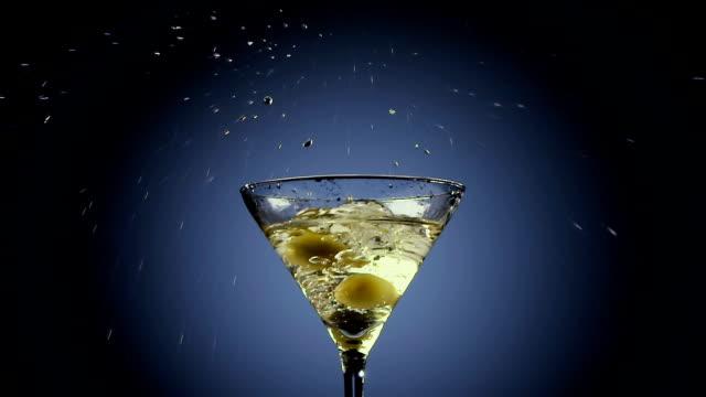 stockvideo's en b-roll-footage met twee olijven vallen in hoge martiniglas. zwarte achtergrond - martini