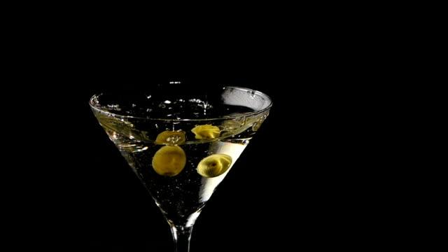 due olive cadere in un bicchiere da martini.  rallentatore - martini video stock e b–roll