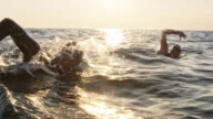 istock SLO MO TS Two open water swimmers swimming front crawl at choppy sea in sunshine 1024439766