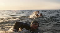 istock SLO MO TS Two open water swimmers swimming front crawl at sea in sunshine 1024406378