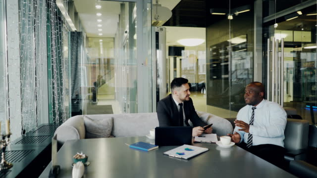 Two optimistic male entrepeneurs in formal clothes discussing their startup project in cafe. African American and Caucasian businessmen talking and sitting at the table video