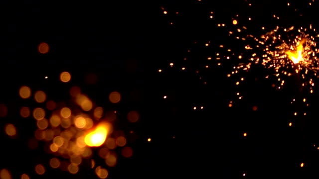 Two orange sparklers against dark background. Super slow motion shallow focus video, 500 fps video