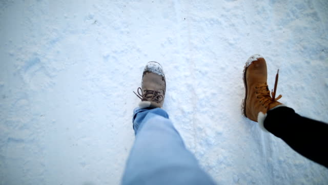 vídeos de stock e filmes b-roll de two pairs of boots hiking on the snow - bota