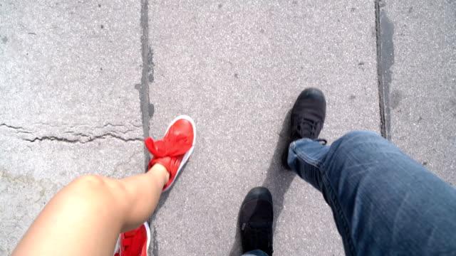 vídeos y material grabado en eventos de stock de pov dos pares de zapatos caminando en la calle - coordinación