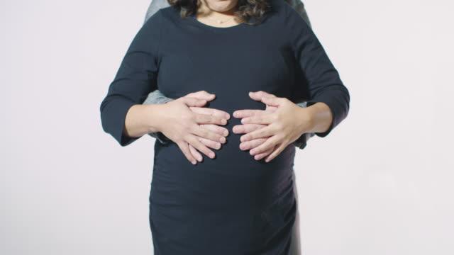 vidéos et rushes de deux parents aiment concept chaque holding mains rub massage sur le ventre de femme enceinte - fête de naissance