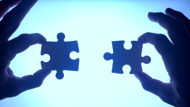 two peaces of puzzle assemble by hands - due oggetti video stock e b–roll