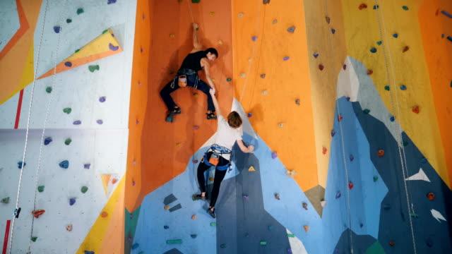 zwei personen klettern auf eine künstliche trainingswand - bouldering stock-videos und b-roll-filmmaterial