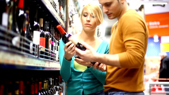 Two people buying wine in supermarket. video