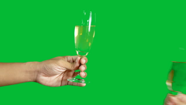 4K. two people clinking each other's with glass of champagne isolated on chroma key green screen background