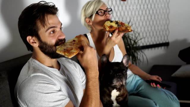 Two people eating pizza and watching TV - video