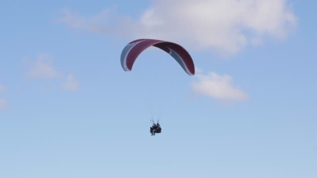 Two People Flying Paraglider. Extreme Paraglider Flying Against Clear Blue Sky. Paragliding Tandem. Extreme Sport.