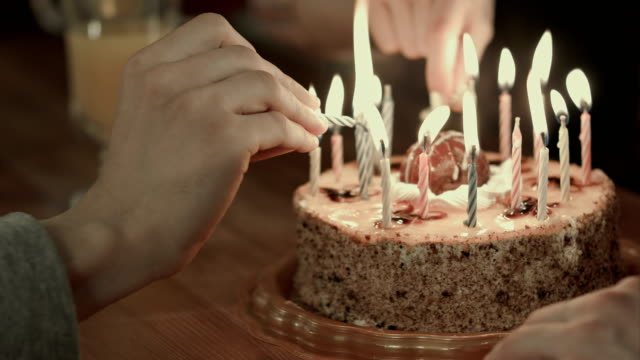Two people lighting the candels on a birthday cake video