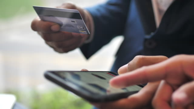 Two people shopping online on Smart phone Two people shopping online on Smart phone gold card stock videos & royalty-free footage