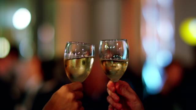 2人はパーティーでシャンパンのグラスで乾杯し、誕生日パーティーやビジネスの採用で歓声を上げました。 - グラス点の映像素材/bロール