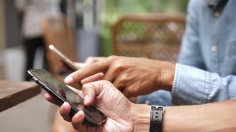 vídeos de stock, filmes e b-roll de duas pessoas telefone usando social media - smartphone