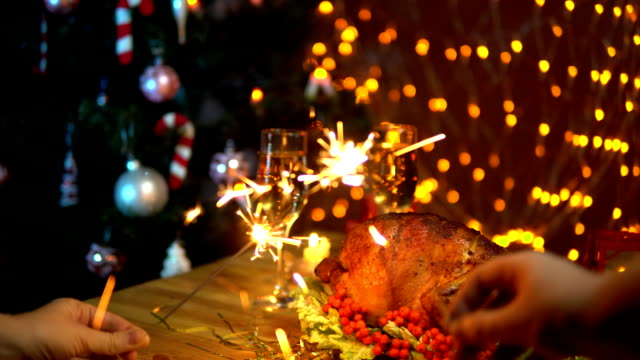 Two people waving sparklers over a festive Christmas table video