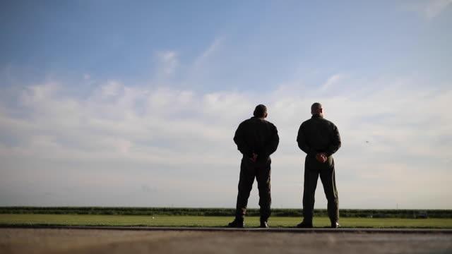 vídeos y material grabado en eventos de stock de dos pilotos mirando el horizonte por encima de la pista - air force
