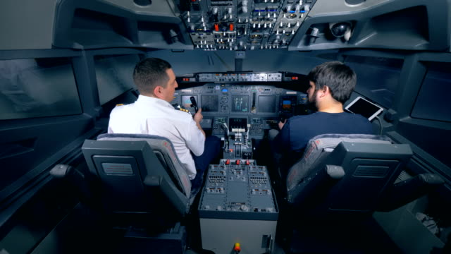 two pilots sit in the cockpit. - pilota video stock e b–roll