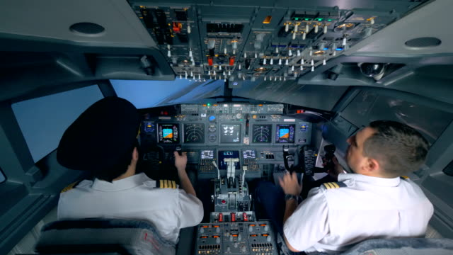 Two pilots turn the plane in a flight simulator. video
