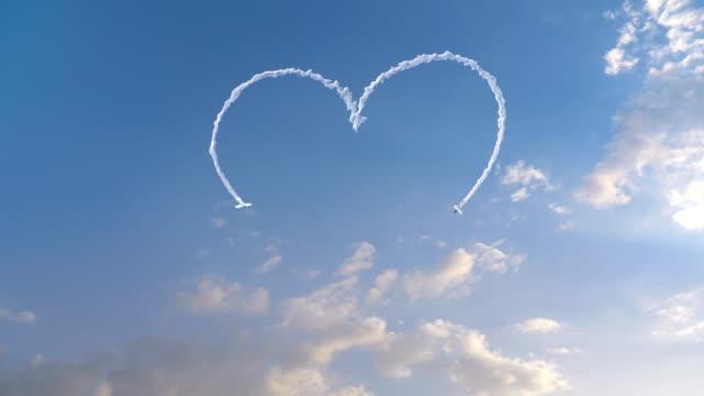 兩架飛機用煙霧把一顆心吸引在天空中 - 愛 個影片檔及 b 捲影像