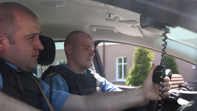Two police in the car talking on the radio