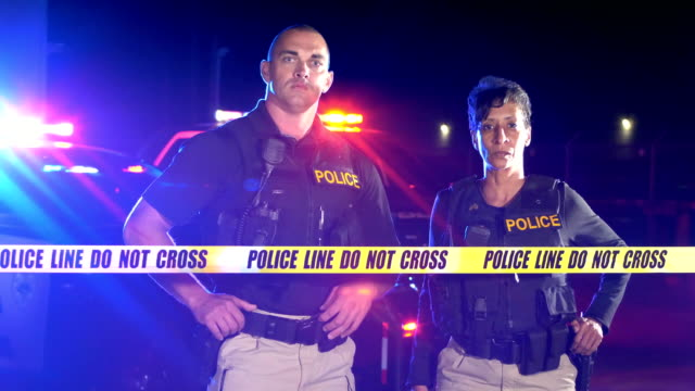 Two police officers walk up to crime scene tape