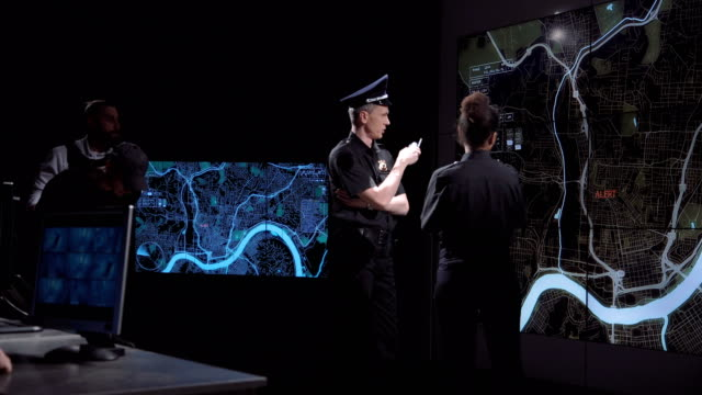 Two police officers watching a digital map video