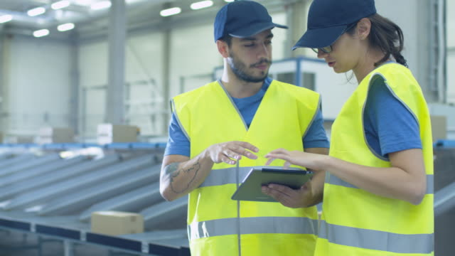 Two Post Sorting Center Workers Using Tablet while Having Conversation. Two Post Sorting Center Workers Using Tablet while Having Conversation. Shot on RED Cinema Camera in 4K (UHD). post structure stock videos & royalty-free footage